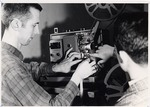 Student with 16MM Motion Picture Projector