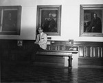 President Quincy V. Doudna Posing With Portraits Of His Predecessors